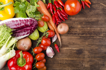 vegetarian diet with fresh and varied vegetables on the old wooden table with empty space for text
