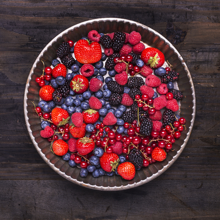 tray with fresh and colorful berries on rustic dark wood background