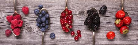 set of fresh fruit arranged in spoons on rustic wooden table Reklamní fotografie