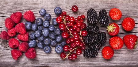 set of fresh forest fruits arranged on rustic wooden table Reklamní fotografie