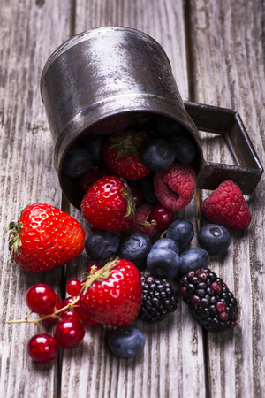 metal mug with mix of berries on rough wooden table