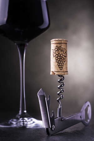 closeup of a corkscrew with cork, in the background a goblet of red wine