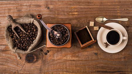 grinder with coffee cup on wooden background