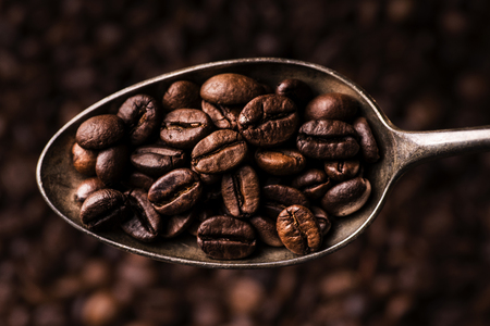 closeup of a spoon full of toasted coffee beans Imagens