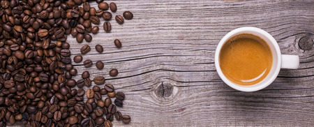 an old rustic wooden table with coffee beans and a cup of espresso