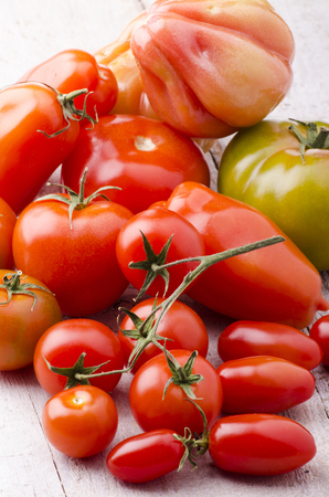 group of fresh tomatoes freshly picked laid on light wooden table
