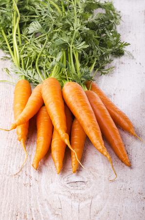 Orange fresh carrots with green tuft on light wood table