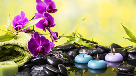 Zen garden with black stones, purple orchid and floating candles Imagens