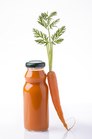 carrot juice in a glass bottle and whole carrots with white background Imagens