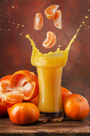 cloves of clementine fall into a full glass of juice creating a splash