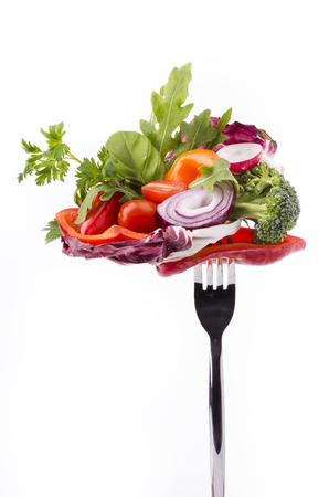 tasty mixed salad with fresh organic ingredients on a white background