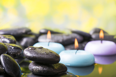 Zen garden with black stones and floating candles