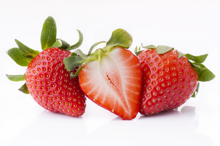 macro of fresh whole strawberries and sliced on the white background