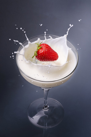 strawberry falling into a glass full of milk with splash Imagens