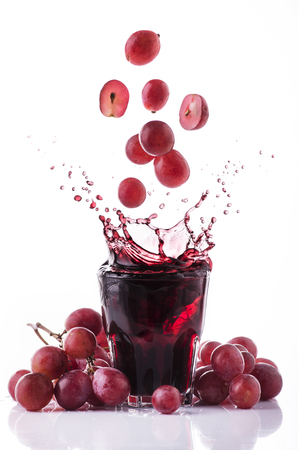 bunch of red grapes and fresh grape juice on a white background