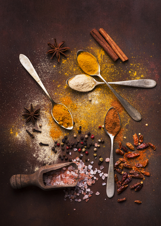 mixed ingredients and colorful and fragrant spices on a dark background