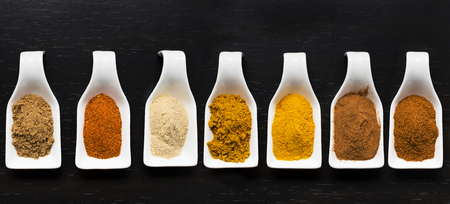 assortment of brightly colored spices in white ceramic bowls on a black background