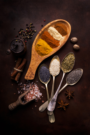 still life with colorful spices and seeds in wooden bowl