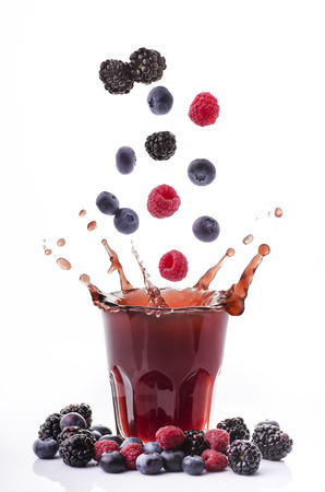 berries fall into a glass with juice generating a splash Imagens