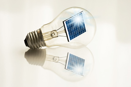 energy concept. Light bulb with a solar panel inside isolated from the white background
