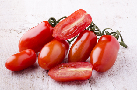 bunch of freshly picked San Marzano tomatoes laid down on a light wooden table