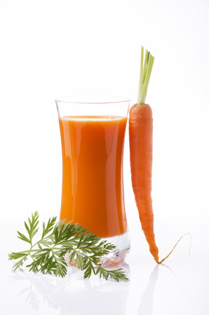 fresh carrot juice in glass beaker and whole carrots with white background