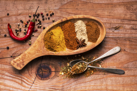 assortment of brightly colored spices in wooden bowl on rough background