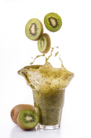 slices of kiwi fall into a glass of fresh kiwi smoothie Imagens