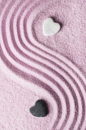 two stone-shaped hearts one white and the other black on pink sand Stock Photo