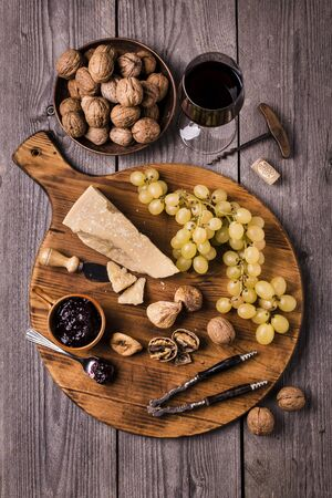 wooden chopping board with seasoned cheese, dried figs, wine walnuts and bunches of table grapes