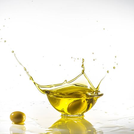 some green olives fall into a bowl full of olive oil with splash. White background