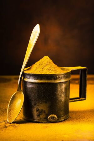 still life, closeup of turmeric powder on the table and in the vintage metal measuring spoon Imagens