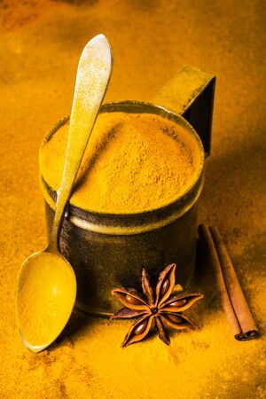 still life, closeup of turmeric powder on the table and in the vintage metal measuring spoon