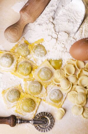 ravioli, homemade egg pasta, freshly prepared, Italian regional recipe on the table with rolling pin, sieve and ingredients