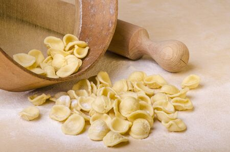 orecchiette, homemade pasta, freshly prepared, Italian regional recipe of Puglia on the table with rolling pin and sieve