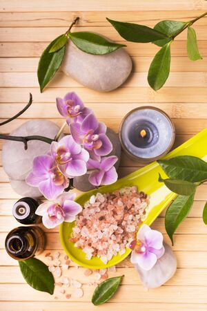 spa.Composition with orchid flowers, some small bottles with essential oil, pink salts, candles and light stones for massage