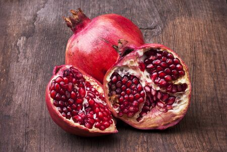still life. Whole pomegranate and a part with seeds on the rough wooden table Reklamní fotografie