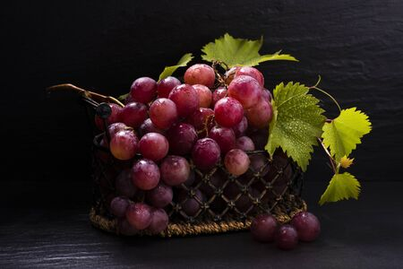 in the vintage basket red table grapes with leaves .still life
