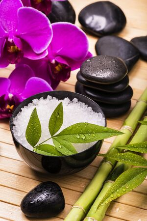 spa.Some black stones with purple orchid flowers, green foliage and a bowl with bath salt