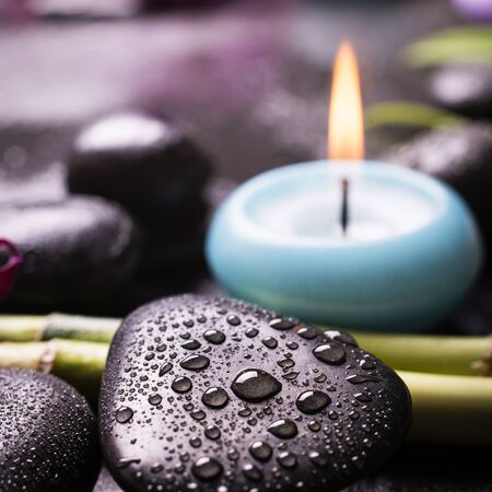closeup of some black stones covered with drops of water, in the background a candle and bamboo stalks