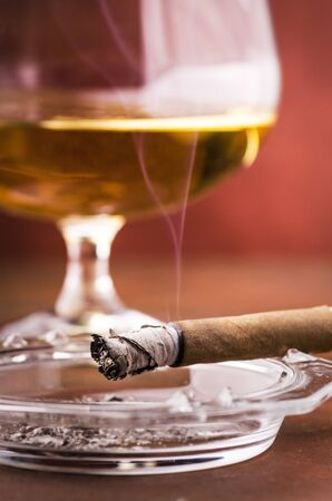 a lit cigar with smoke on ashtray in the foreground, in the background a glass with alcohol