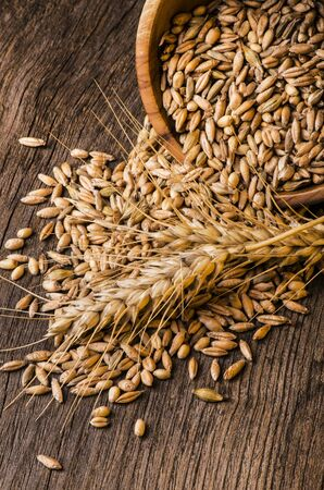 on the wooden table some ears of wheat and cereals Stock fotó