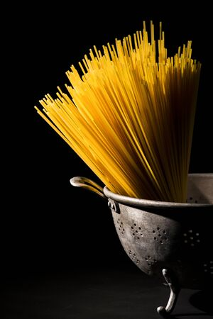 closeup of raw spaghetti laid inside a vintage colander, on a dark background Stock fotó