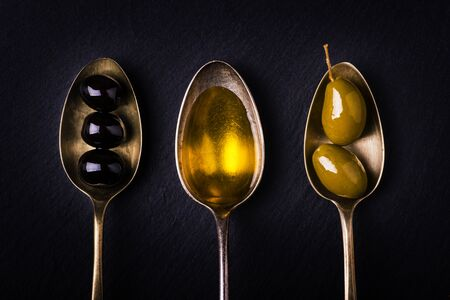 on the slate stone three tablespoons, one full of extra virgin olive oil and the others with green and black olives