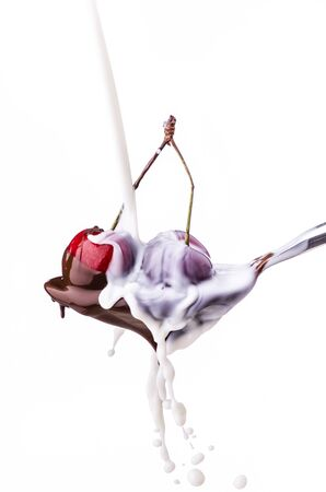 spoon with juicy cherries covered with melted dark chocolate and milk splash Standard-Bild