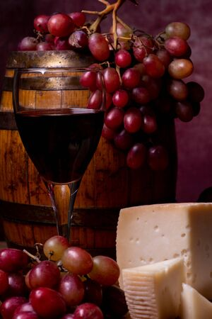 still life. In the foreground, on a old barrel a bunch of red grapes. on the table a glass of wine