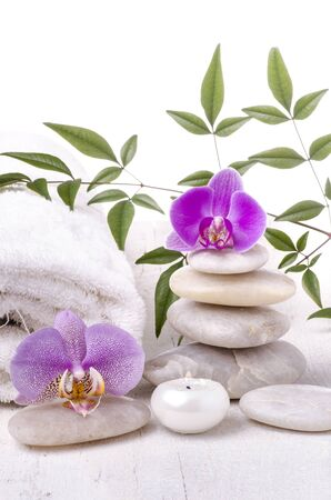 some stacked clear stones, the orchid flowers and a white towel with scented candles