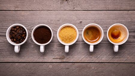 top view of a sequence of cups with coffee beans and ground coffee, sugar cane, and expressed Stockfoto