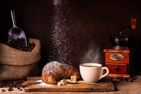 Cup of hot coffee, croassant dusted with veiled sugar, wooden grinder, and jute bag with roasted coffee beans Archivio Fotografico - 137256741