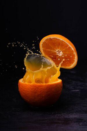 closeup of a fresh orange juice splashed by an orange cut in half on a dark background.